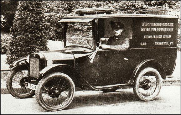 Lieferwagen, Lange Ausführung, um 28 cm länger, mit Dachgepäckständer, Reling, Reserverad vorne auf dem Dach.