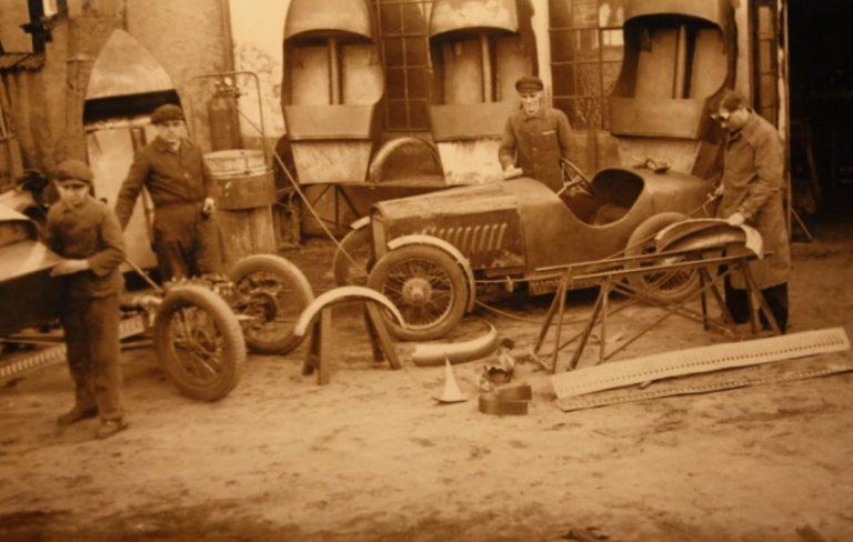Ihle Werkstatt. Im Hintergrund sechs Ihle-Karossen: Ein Dixi-Fahrwerk links, rechts ein sehr früher Ihle 600. An einem linken hinteren Kotflügel werden Schweißarbeiten ausgeführt, im Vordergrund liegen Lochbleche für den Karossen-Unterrand.